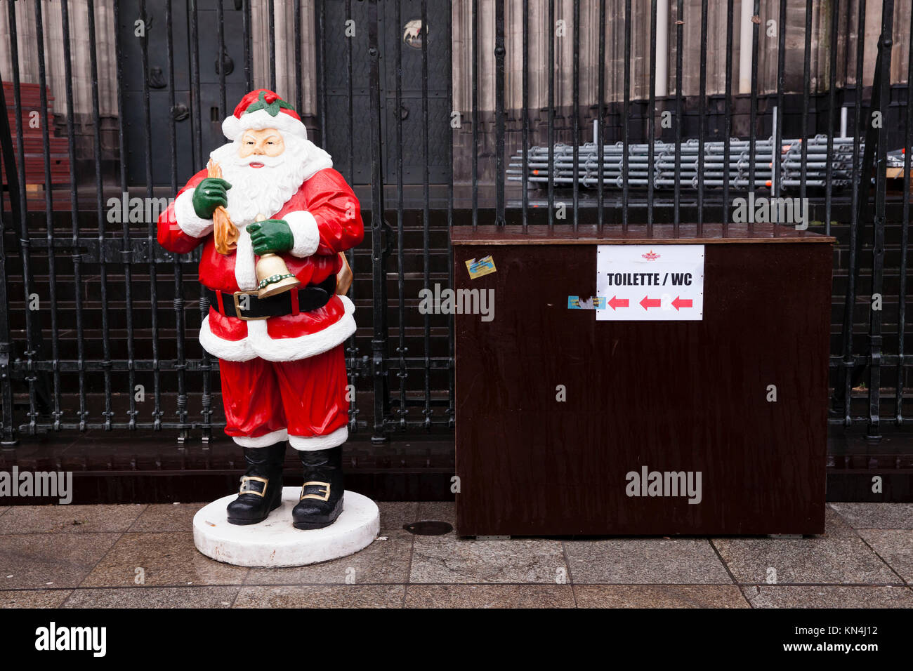 Germany, Cologne, Santa Claus in front of the cathedral, sign to a toilet.  Deutschland, Koeln, Weihnachtsmann vor - Stock Image