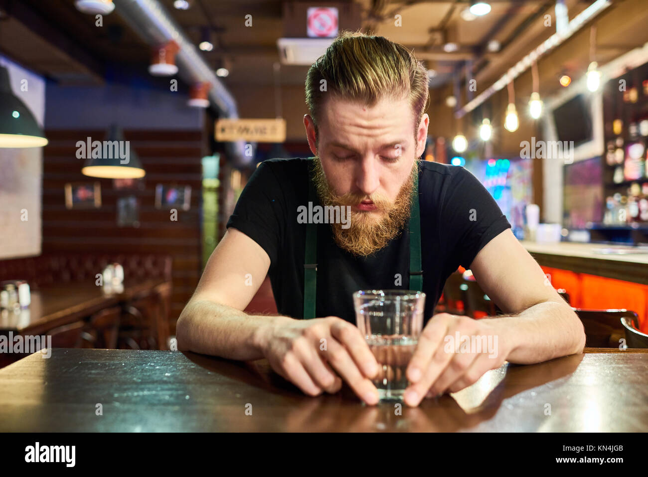 Young Bearded Man Getting Drunk in Bar - Stock Image