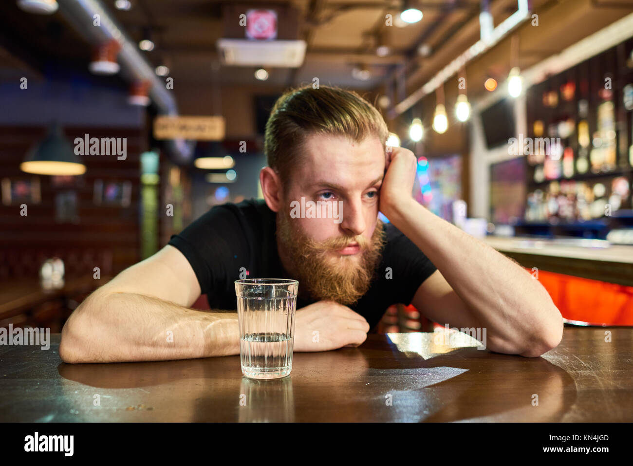 Sad Bearded Man Getting Drunk in Bar - Stock Image