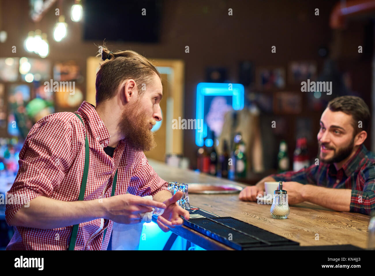 Bartender Talking to Visitor at Pub Counter - Stock Image