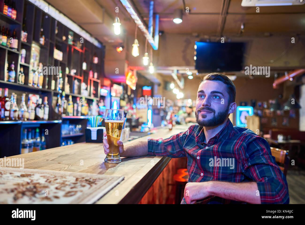 Man Watching TV in Beer Pub - Stock Image