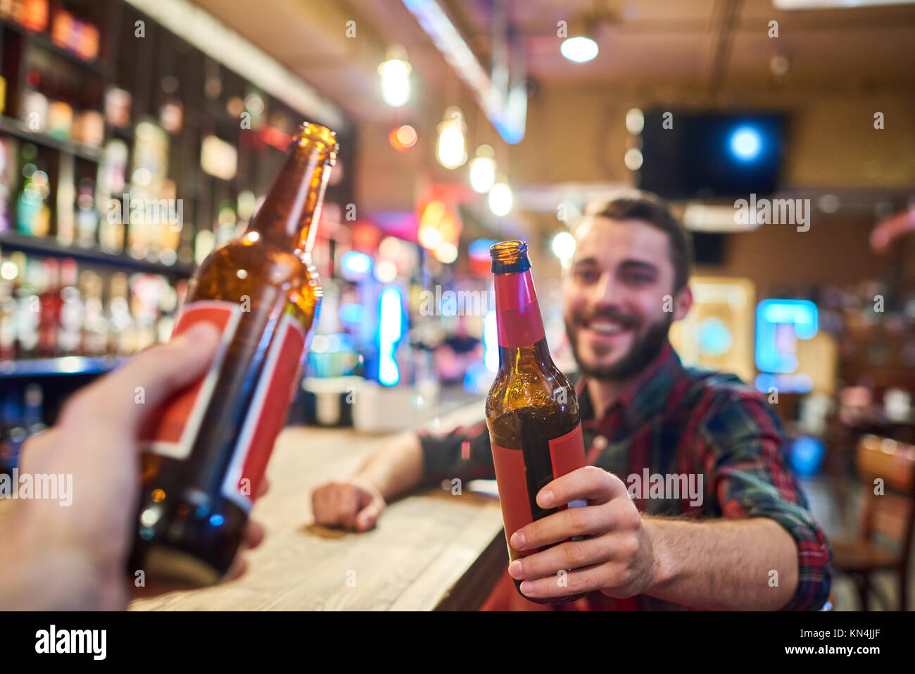 Happy Young Man Clinking Bottles with Friend in Bar - Stock Image