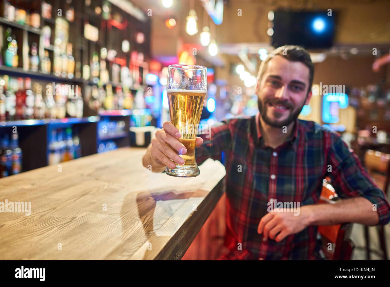 Happy Young Man Cheering at Bar Counter - Stock Image