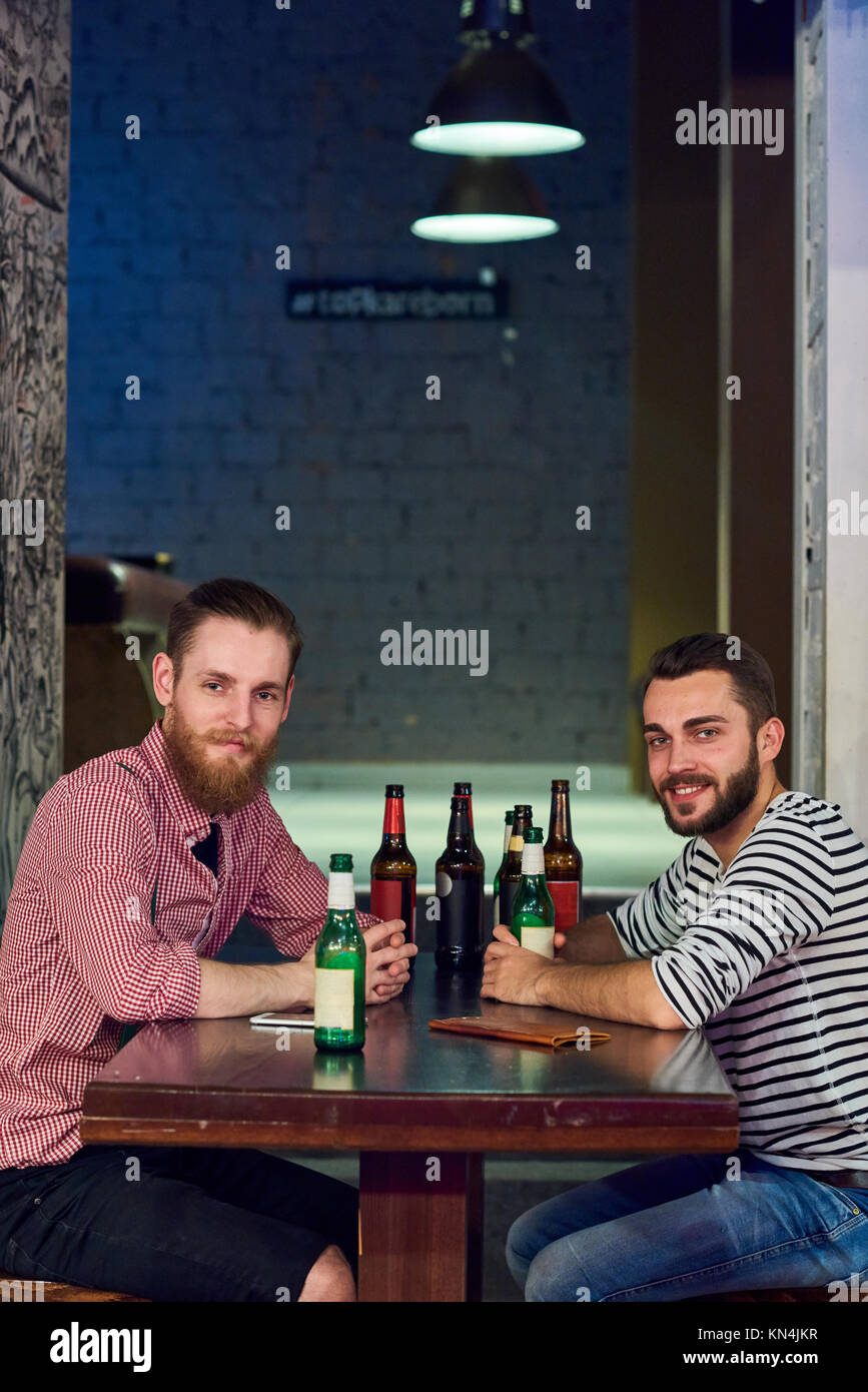 Two Buddies Drinking Beer in Bar - Stock Image