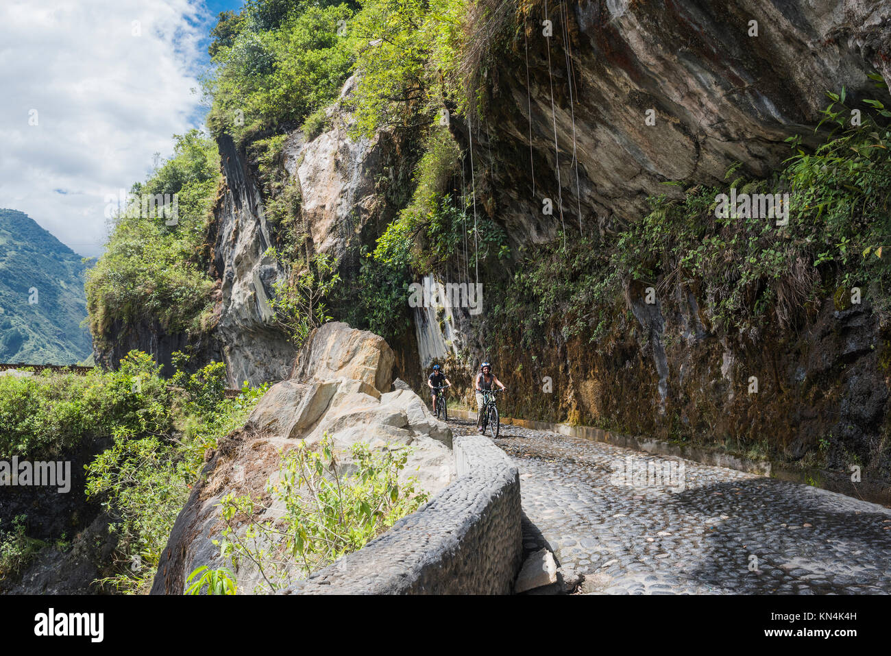 Cascades route, Banos - Puyo, Ecuador - December 8, 2017: Tourists ride bicycles along the Waterfalls Road over - Stock Image
