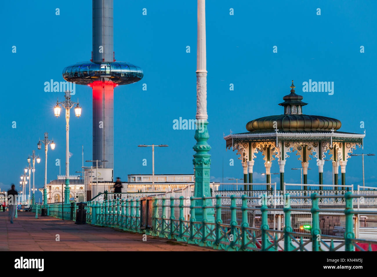 NIght falls on Brighton seafront, UK. Victorian Bandstand and i360 tower in the distance. - Stock Image