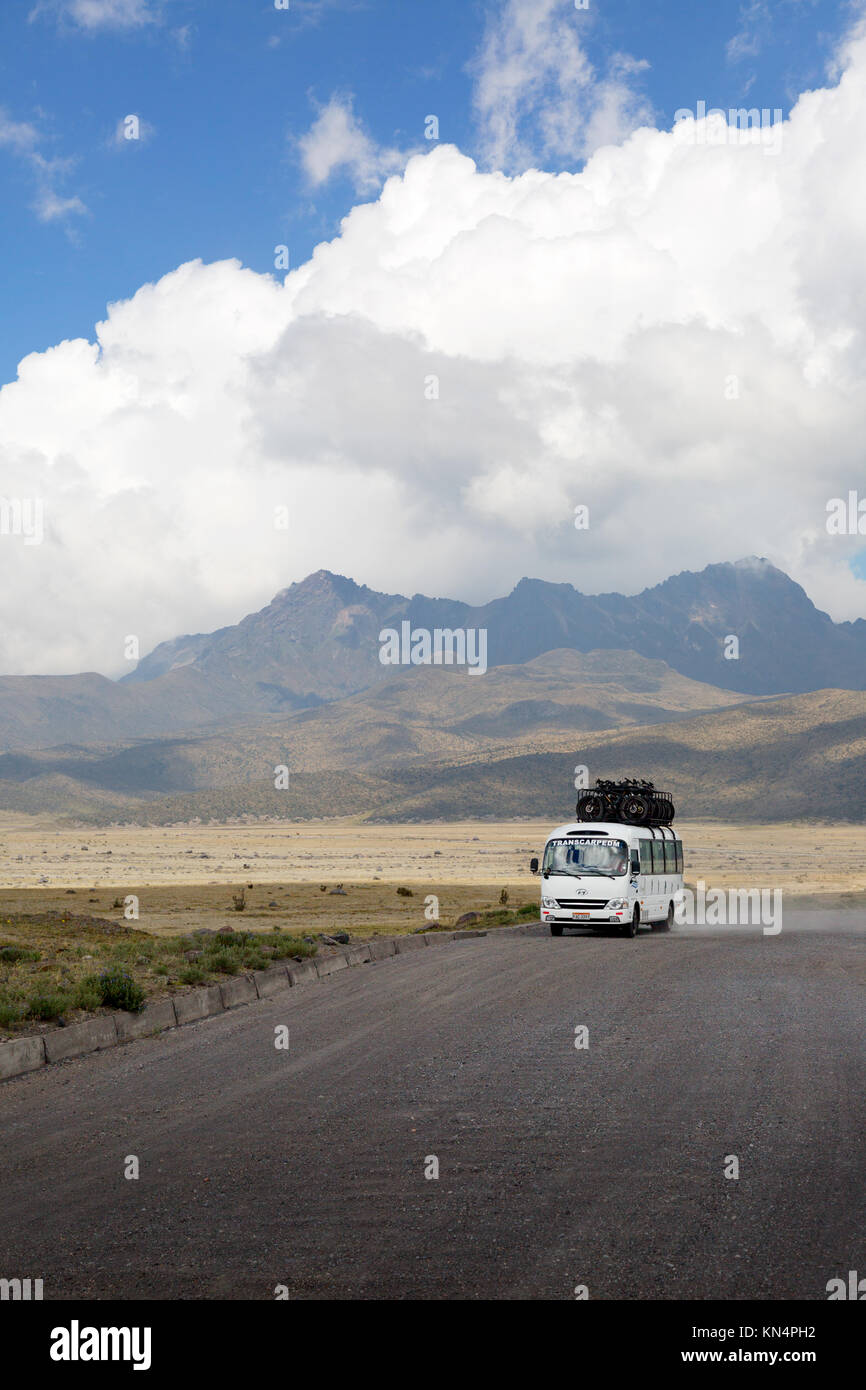 A tour bus driving through Cotopaxi National Park, Ruminahui volcano in the background, Ecuador South America - Stock Image