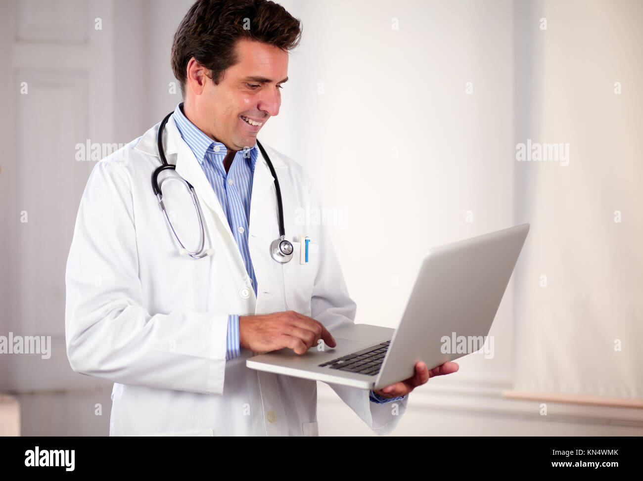 Portrait of a handsome doctor on white coat working on his laptop while standing on hospital. - Stock Image