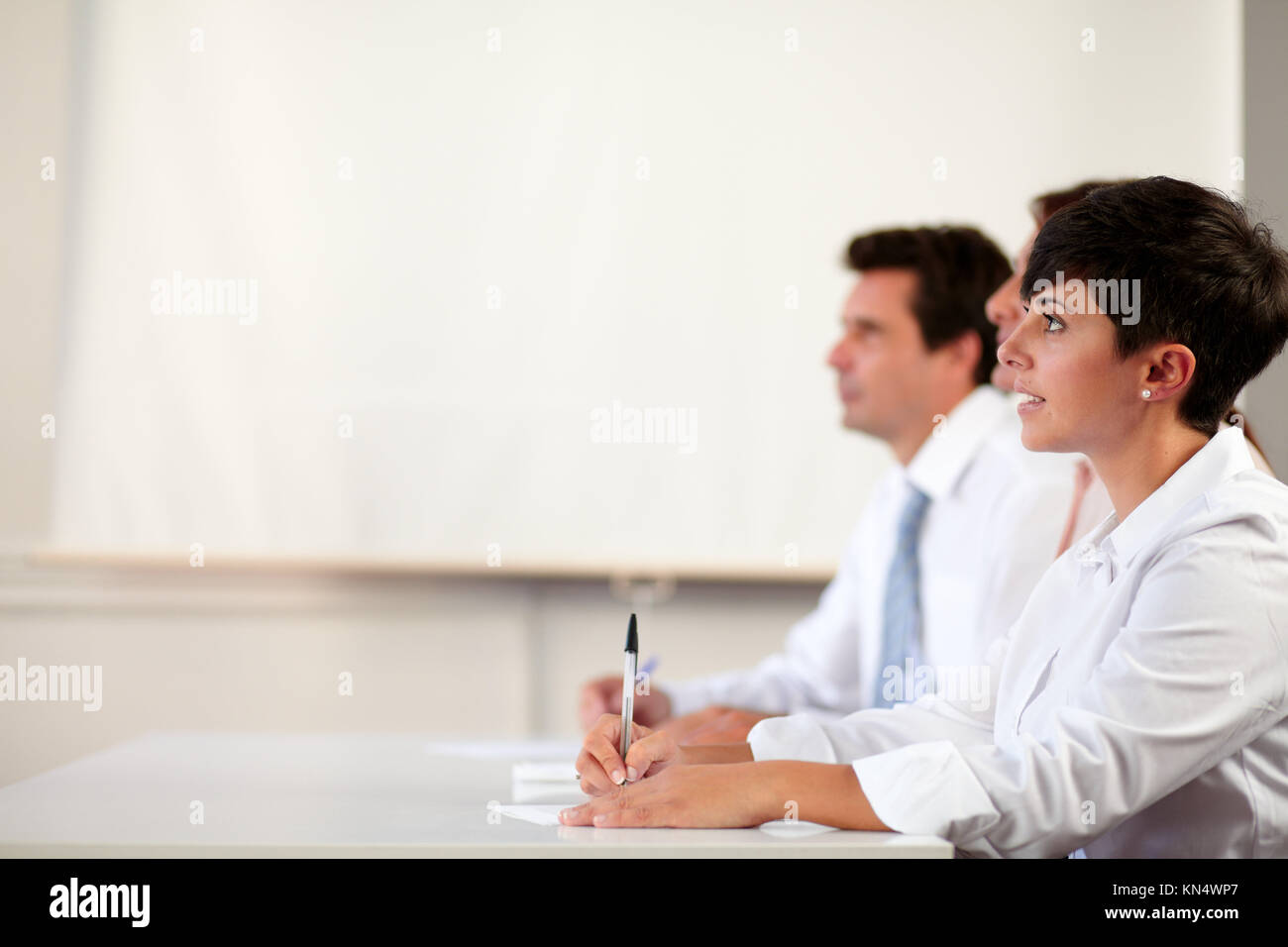 Portrait of a pretty hispanic executive looking at presentation in front of a coworker on office background - copyspace. - Stock Image
