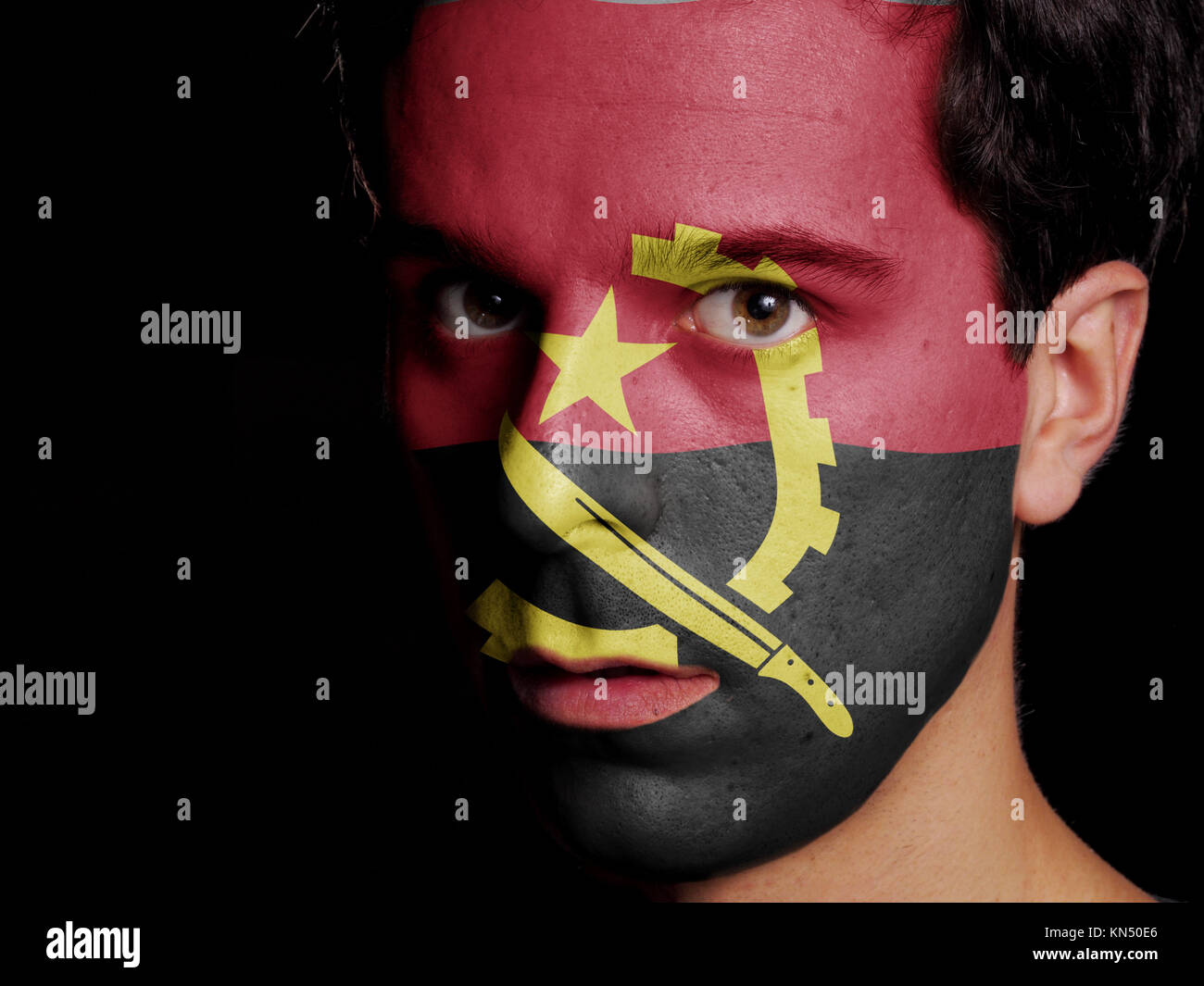 Flag of Angola Painted on a Face of a Young Man. - Stock Image
