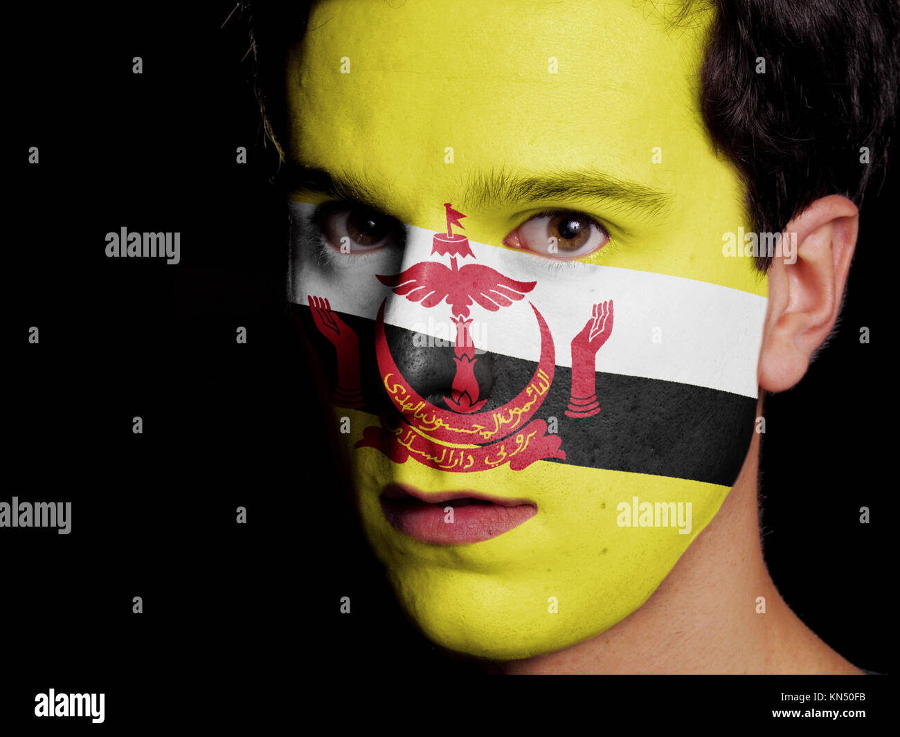 Flag of Brunei Painted on a Face of a Young Man. - Stock Image