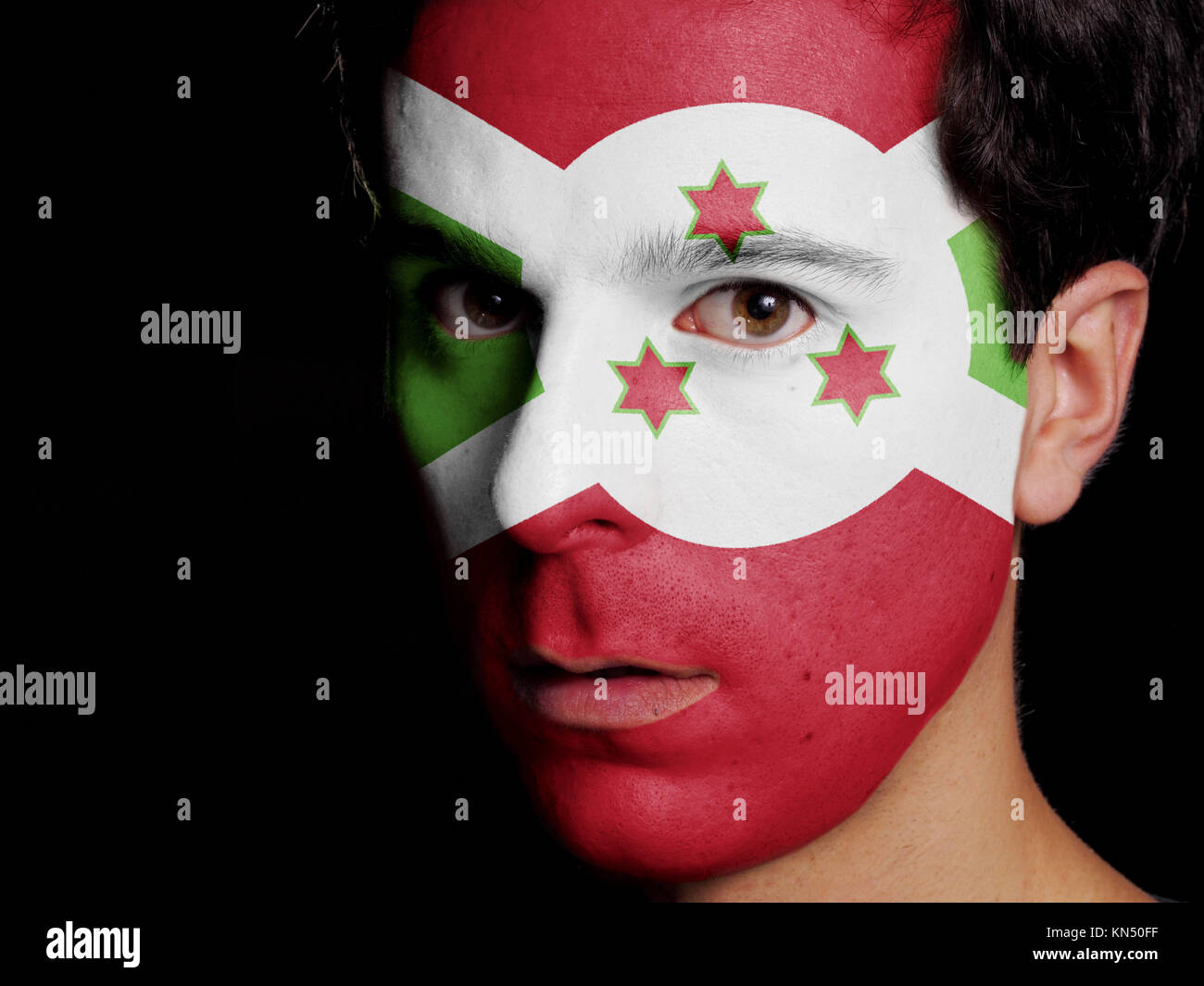 Flag of Burundi Painted on a Face of a Young Man. - Stock Image