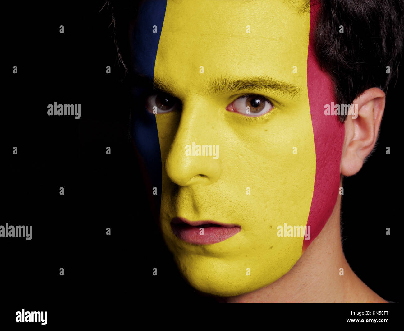Flag of Chad Painted on a Face of a Young Man. - Stock Image