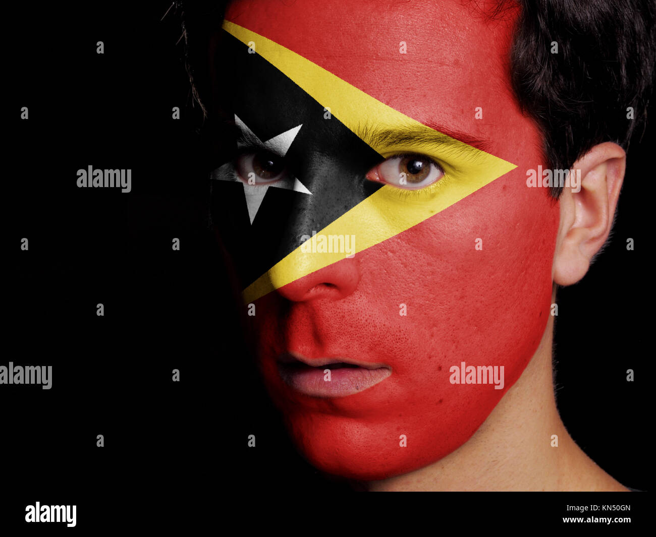 Flag of East Timor Painted on a Face of a Young Man. - Stock Image