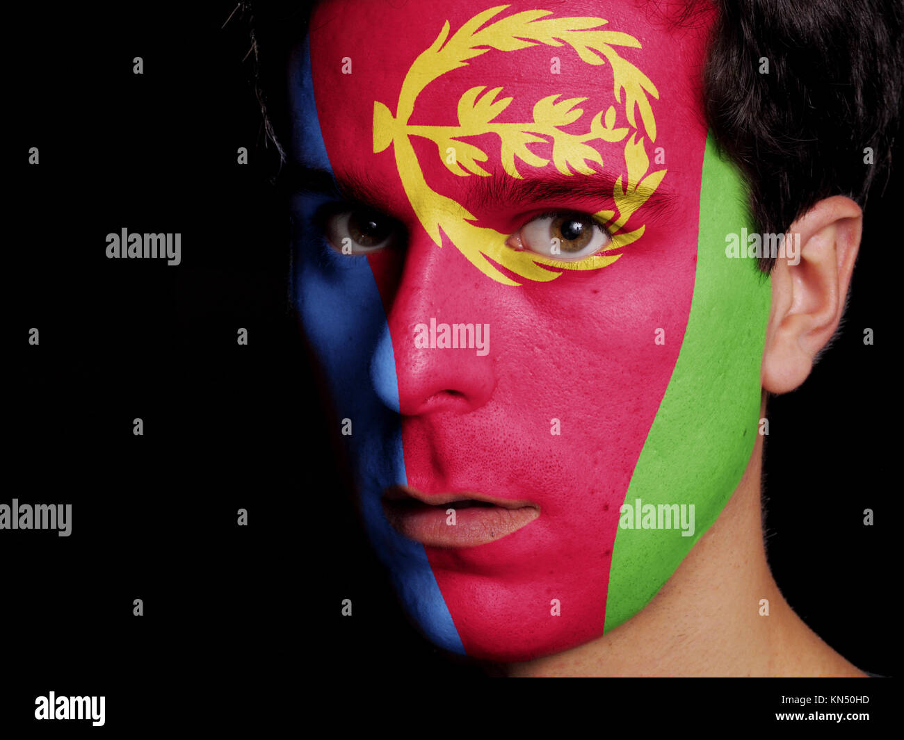 Flag of Eritrea Painted on a Face of a Young Man. - Stock Image