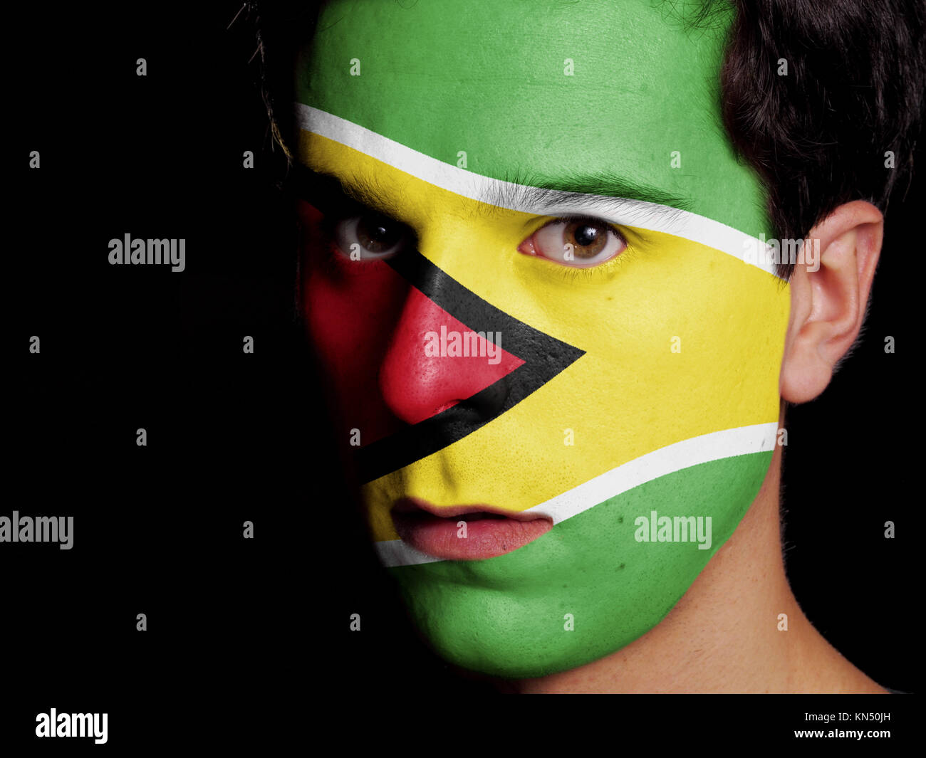 Flag of Guyana Painted on a Face of a Young Man. - Stock Image