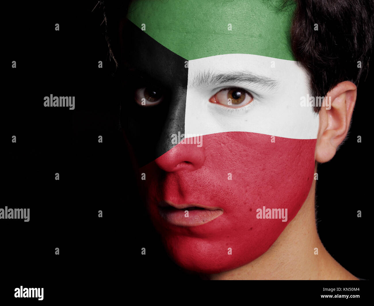 Flag of Kuwait Painted on a Face of a Young Man. - Stock Image