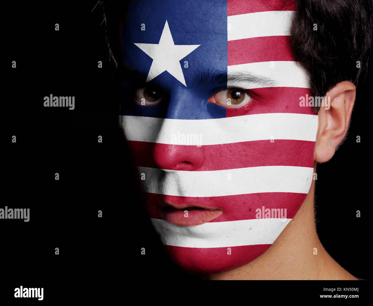 Flag of Liberia Painted on a Face of a Young Man. - Stock Image
