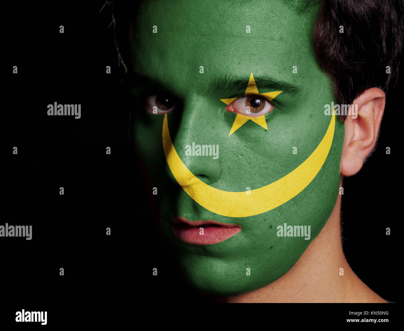 Flag of Mauritania Painted on a Face of a Young Man. - Stock Image