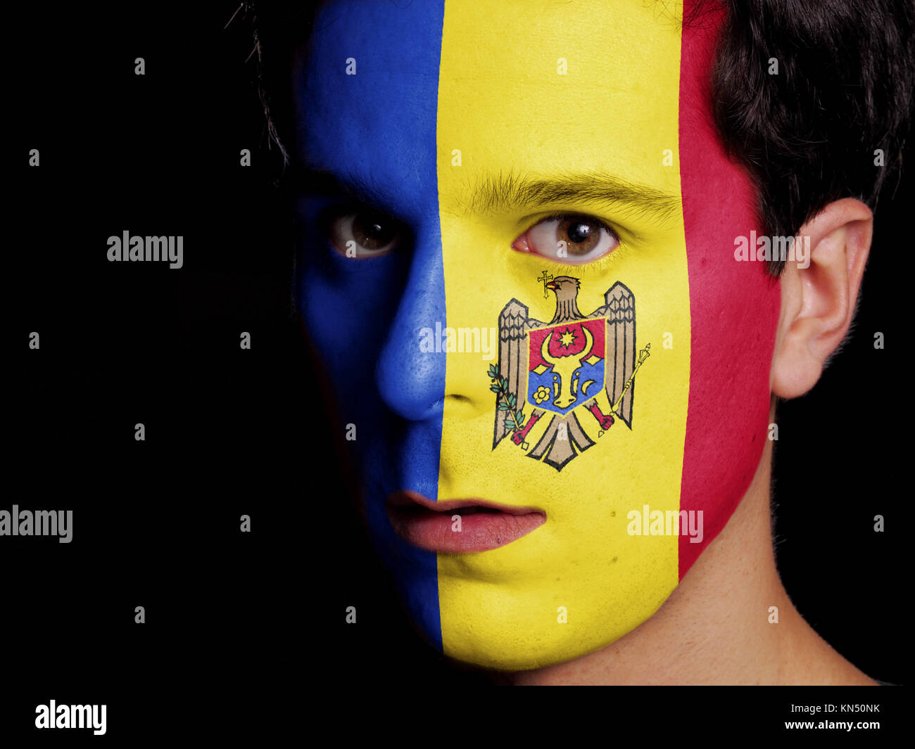 Flag of Moldova Painted on a Face of a Young Man. - Stock Image