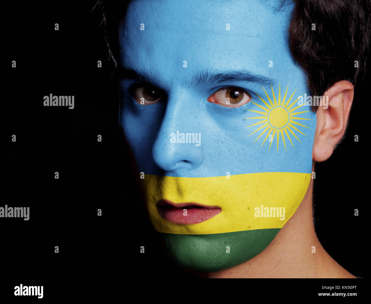 Flag of Rwanda Painted on a Face of a Young Man. - Stock Image