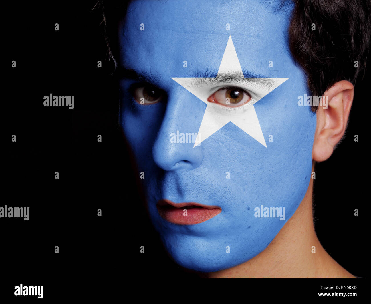 Flag of Somalia Painted on a Face of a Young Man. - Stock Image