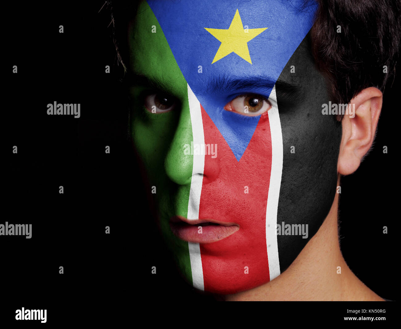 Flag of South Sudan Painted on a Face of a Young Man. - Stock Image