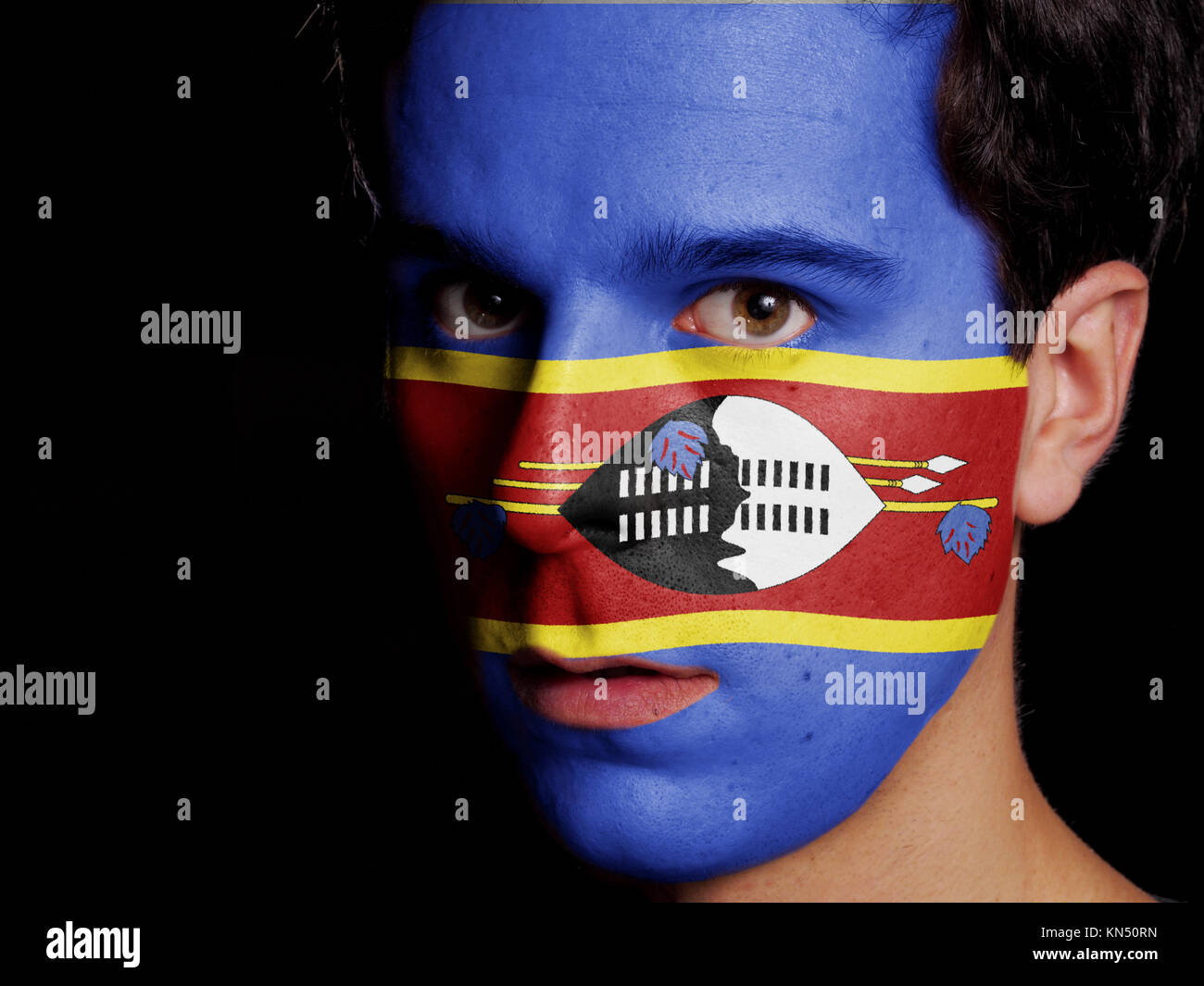 Flag of Swaziland Painted on a Face of a Young Man. - Stock Image