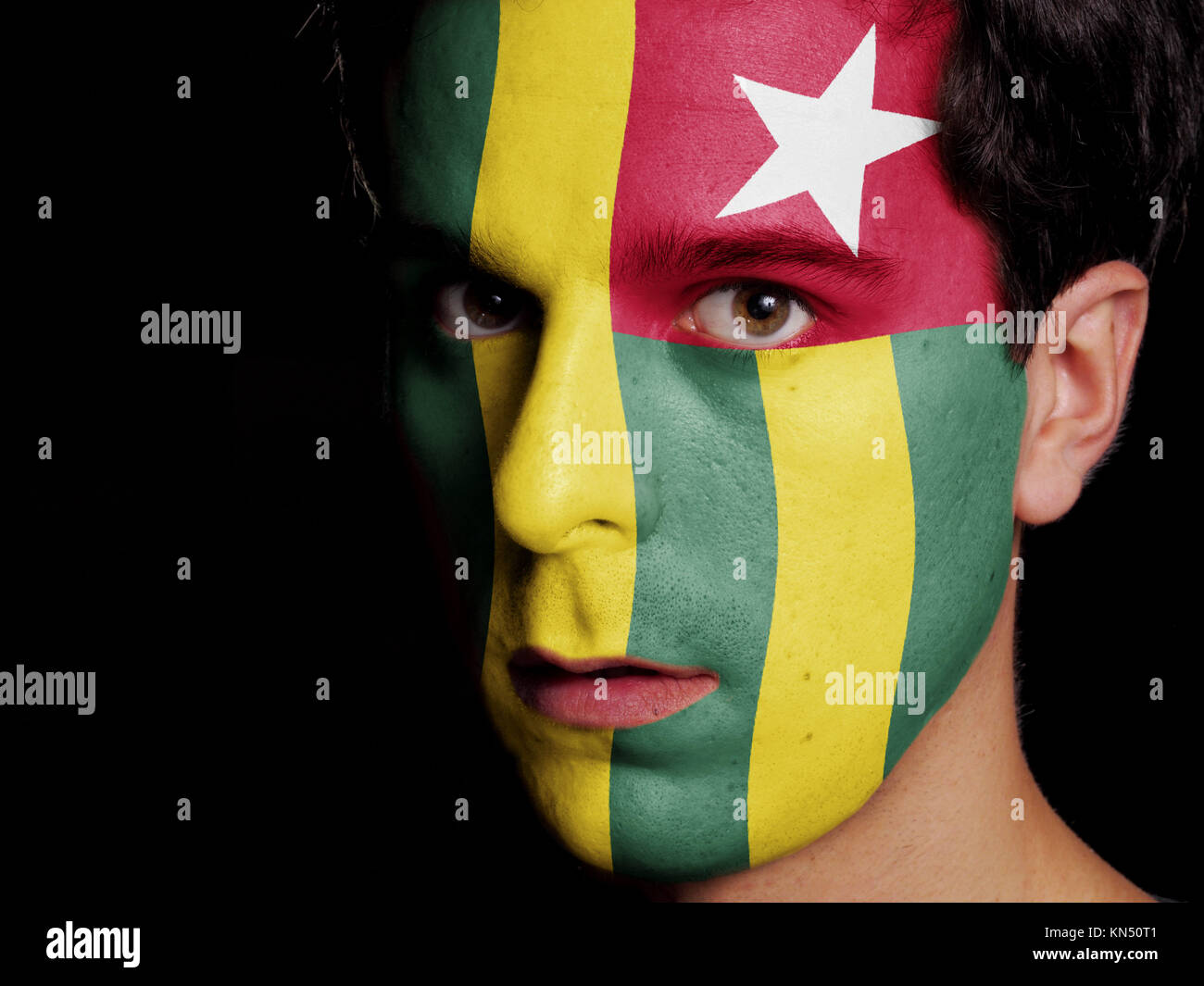 Flag of Togo Painted on a Face of a Young Man. - Stock Image