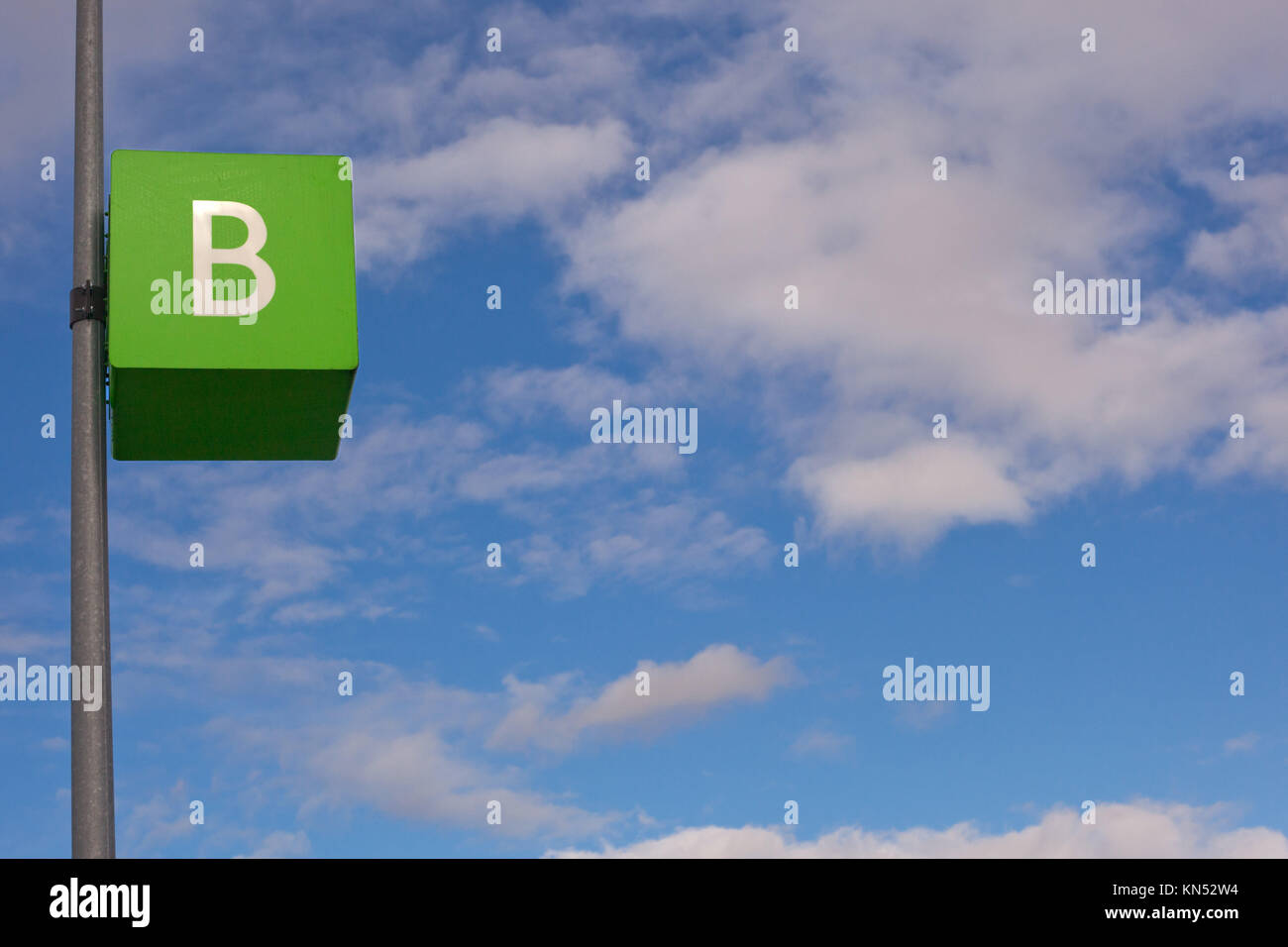 Parking signal pole of letter B area over blue cloudy sky. Stock Photo