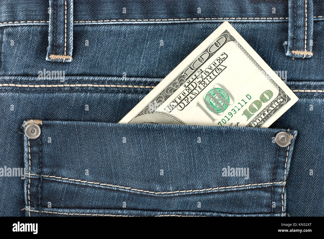 A one hundred dollar note in the back pocket of denim trousers. - Stock Image