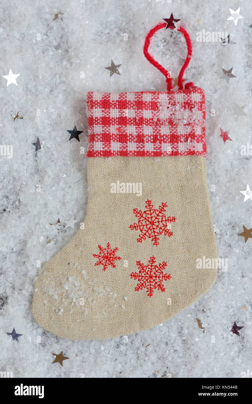 sock with snowflakes for Santa gifts over snow background. - Stock Image