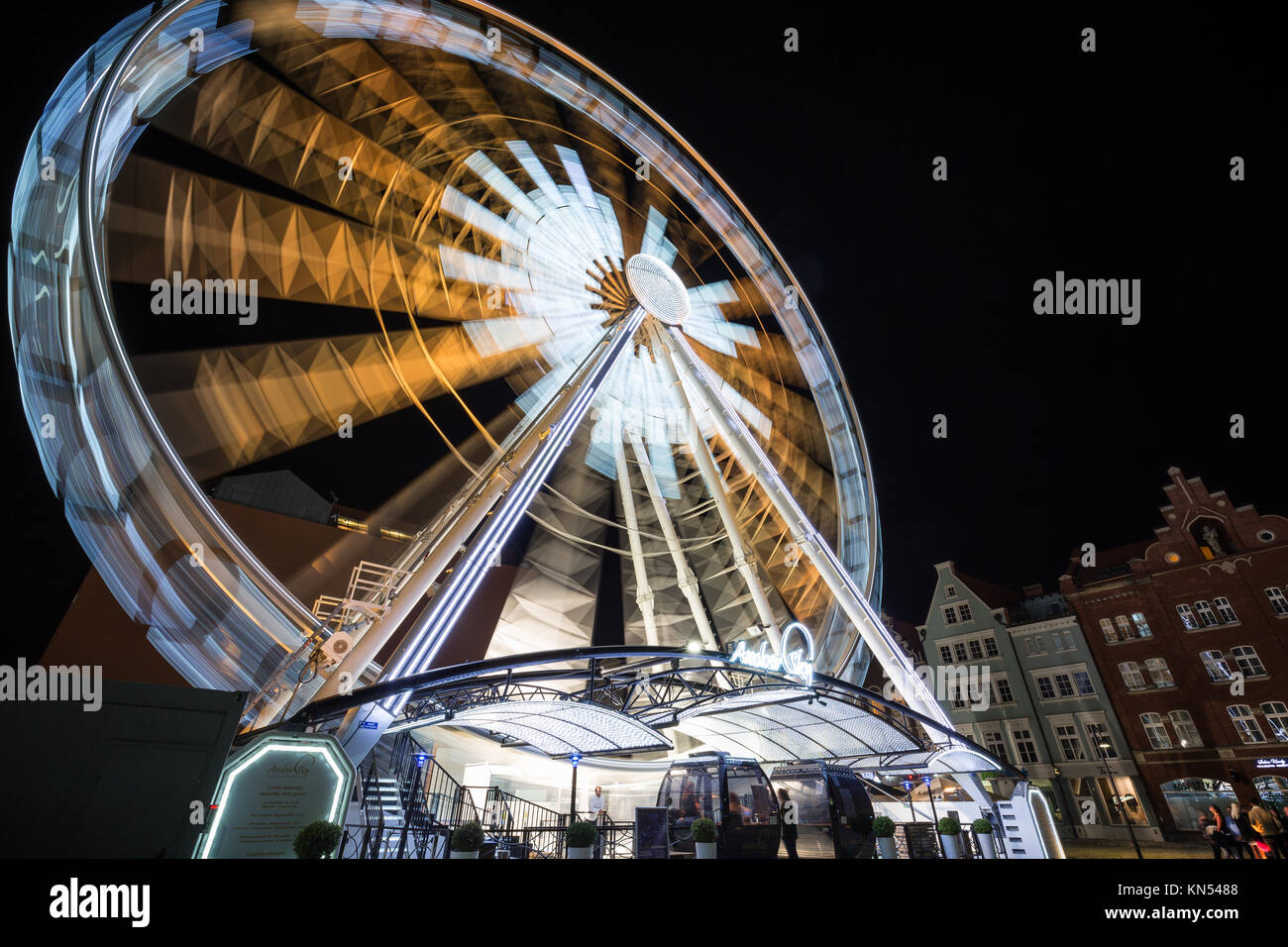 Few people at the lit ferris wheel in motion on the Granary Island in Gdansk, Poland, at night. - Stock Image