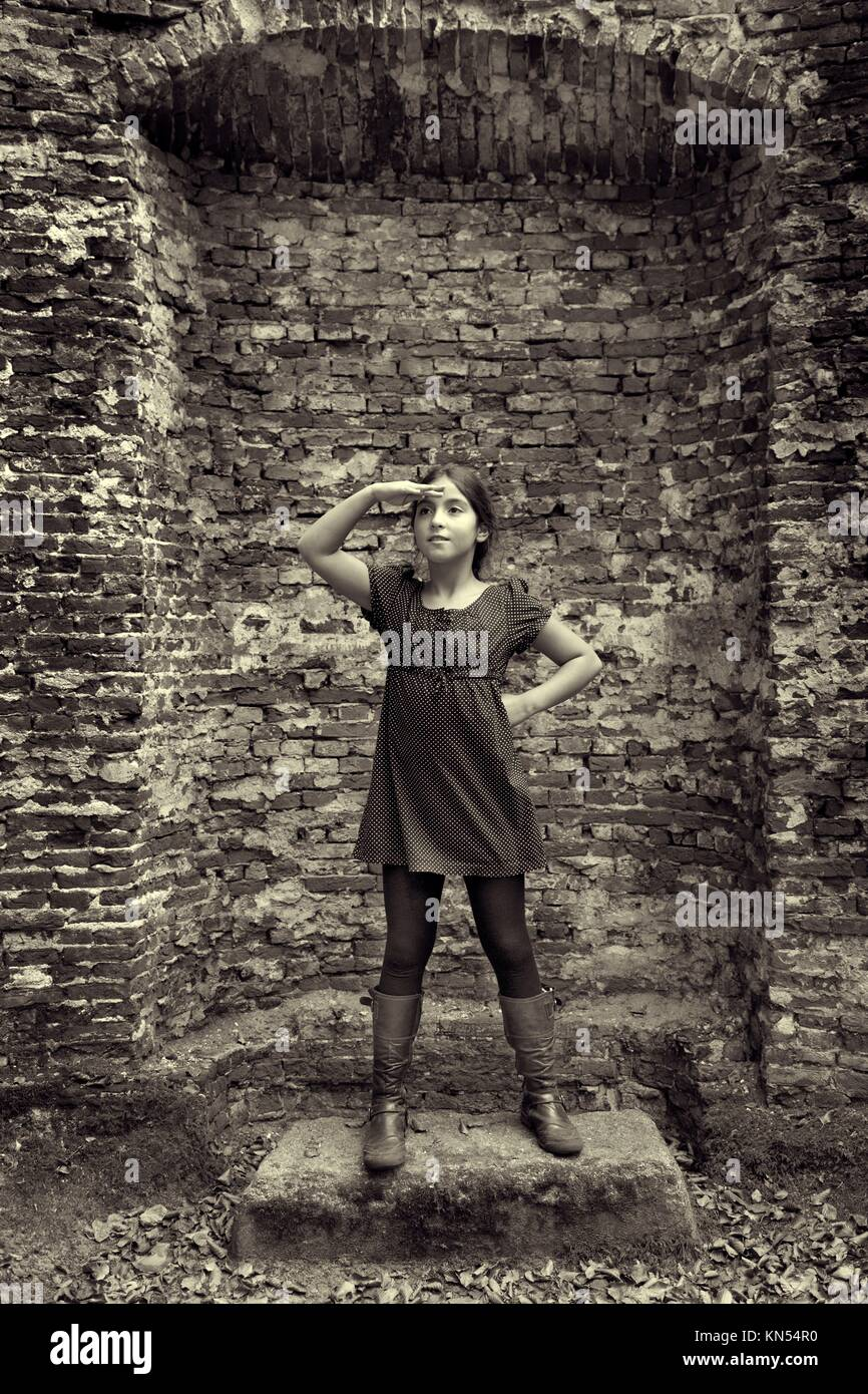 Teenage girl acting as a lady from the past standing in front of the ruin of her castle. - Stock Image