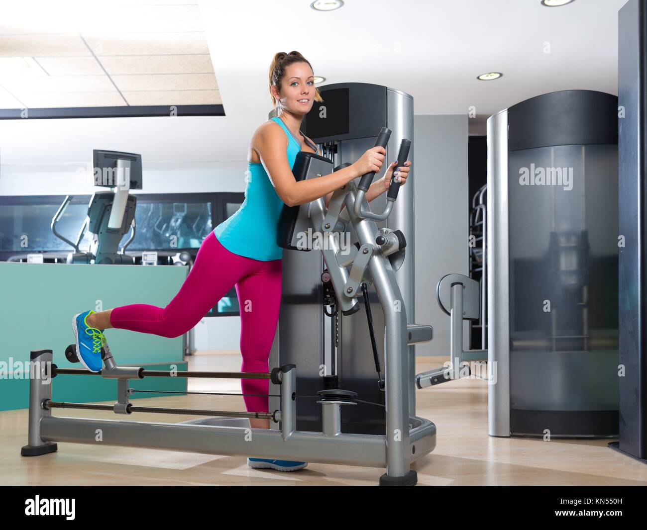 Gym glute exercise machine woman workout indoor. - Stock Image