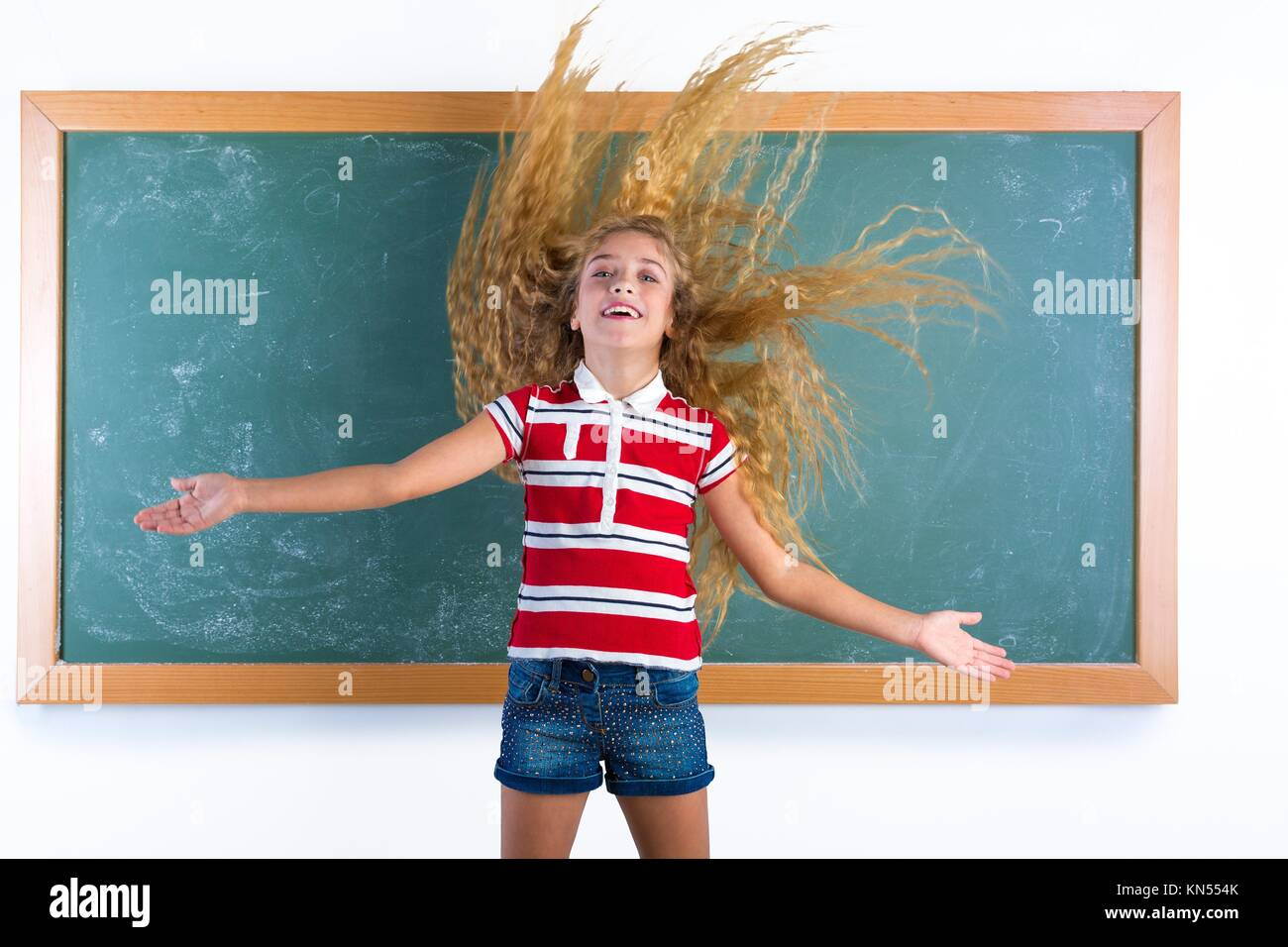 funny student girl flipping long blond hair at school classroom chalk board. - Stock Image