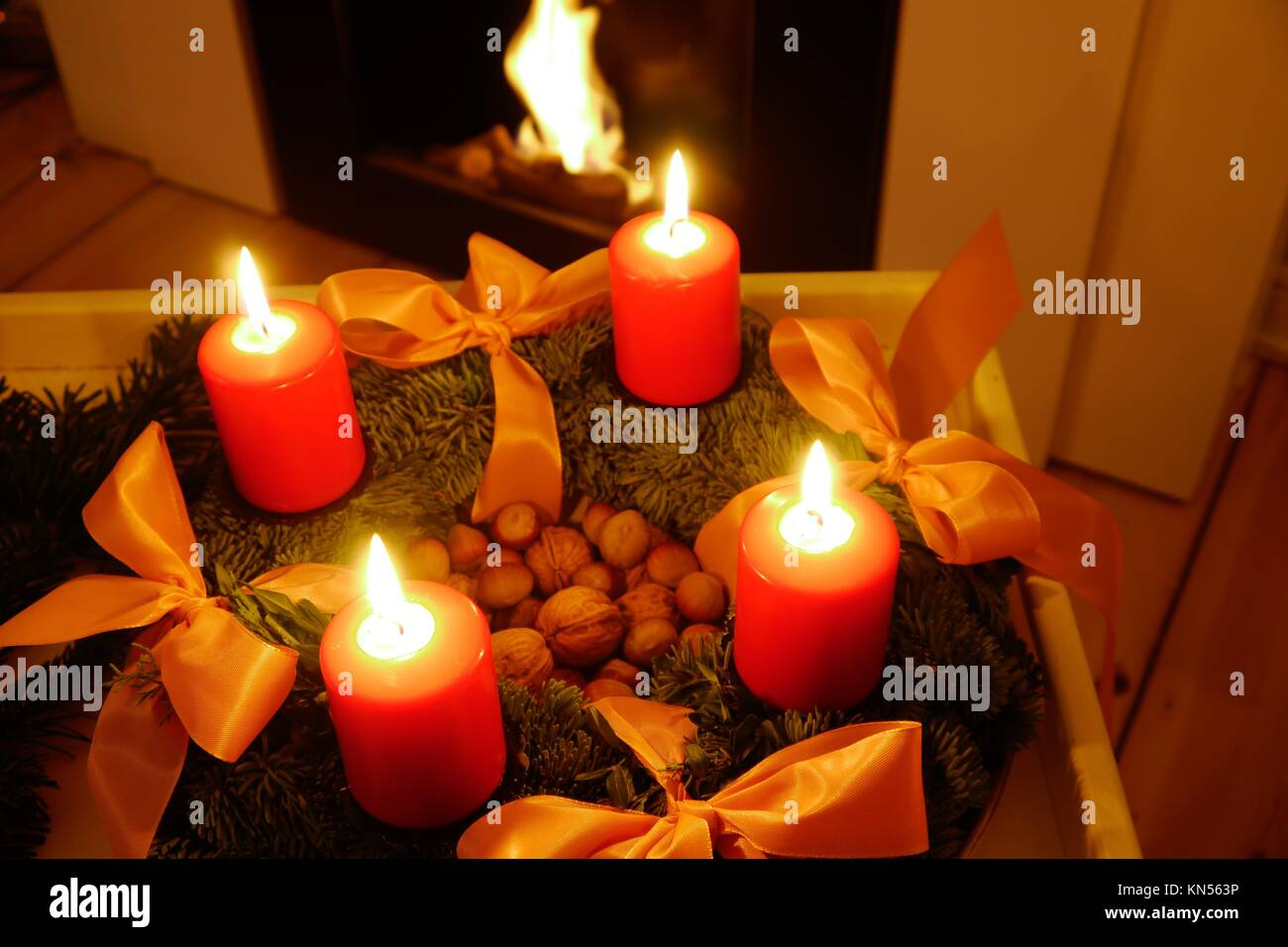 advent wreath with red candles and fireplace. - Stock Image
