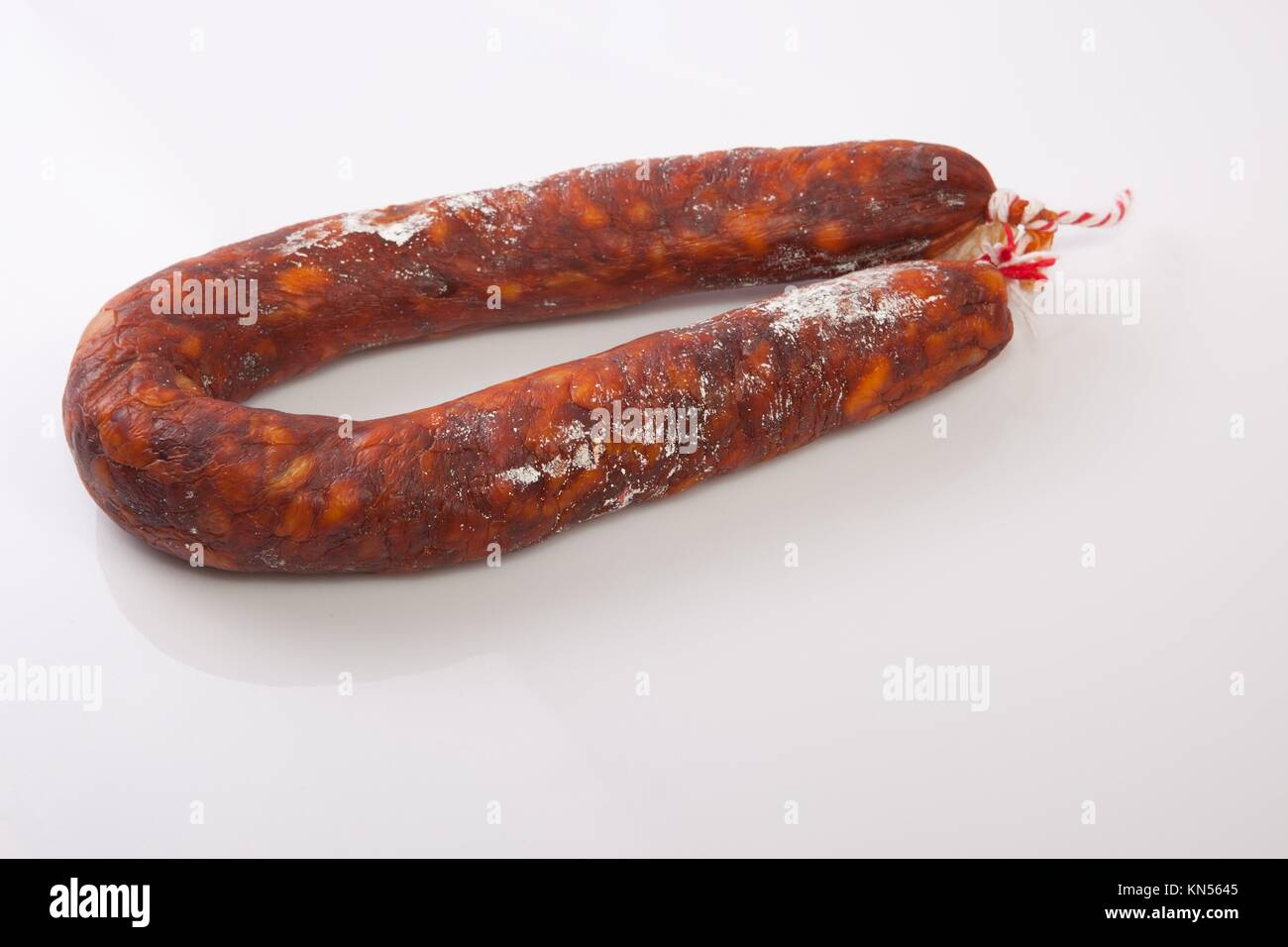 Red spanish chorizo sausage. Isolated over white background. - Stock Image