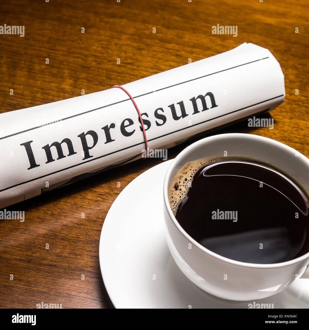 impressum newspaper (german) and cup of coffee. - Stock Image