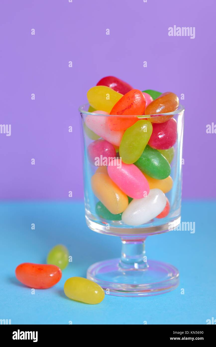 color Jelly Beans in glass on lila background. - Stock Image