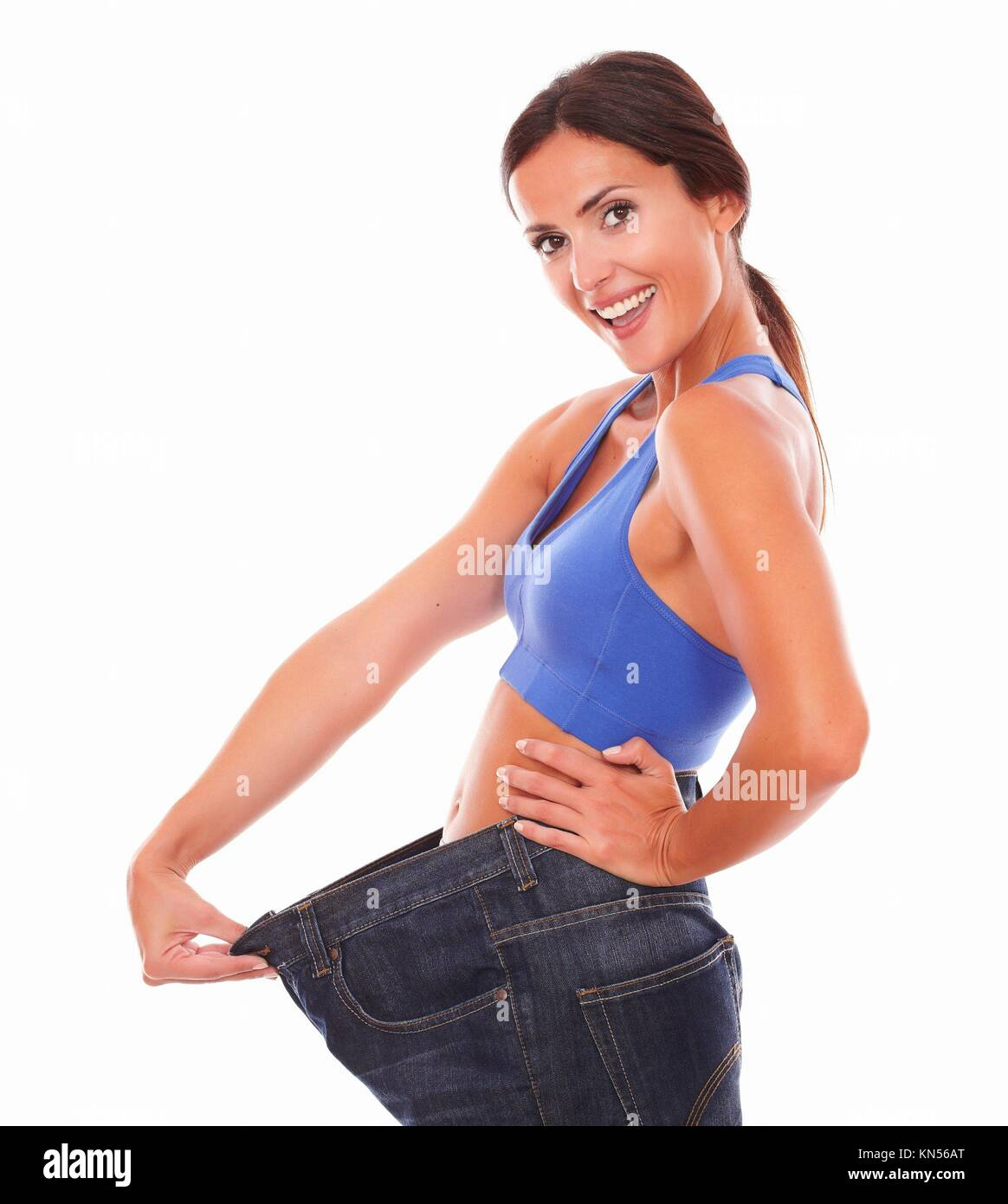 Fit latin woman pulling jeans on waist while looking at you cheerfully with weight loss achievement on isolated - Stock Image
