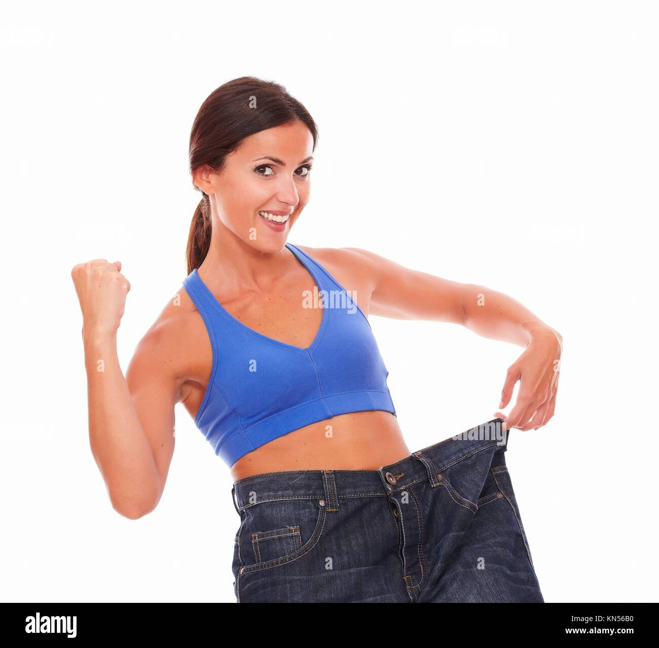 Hispanic brunette cheerfully pulling her jeans to measure waist on isolated background. - Stock Image