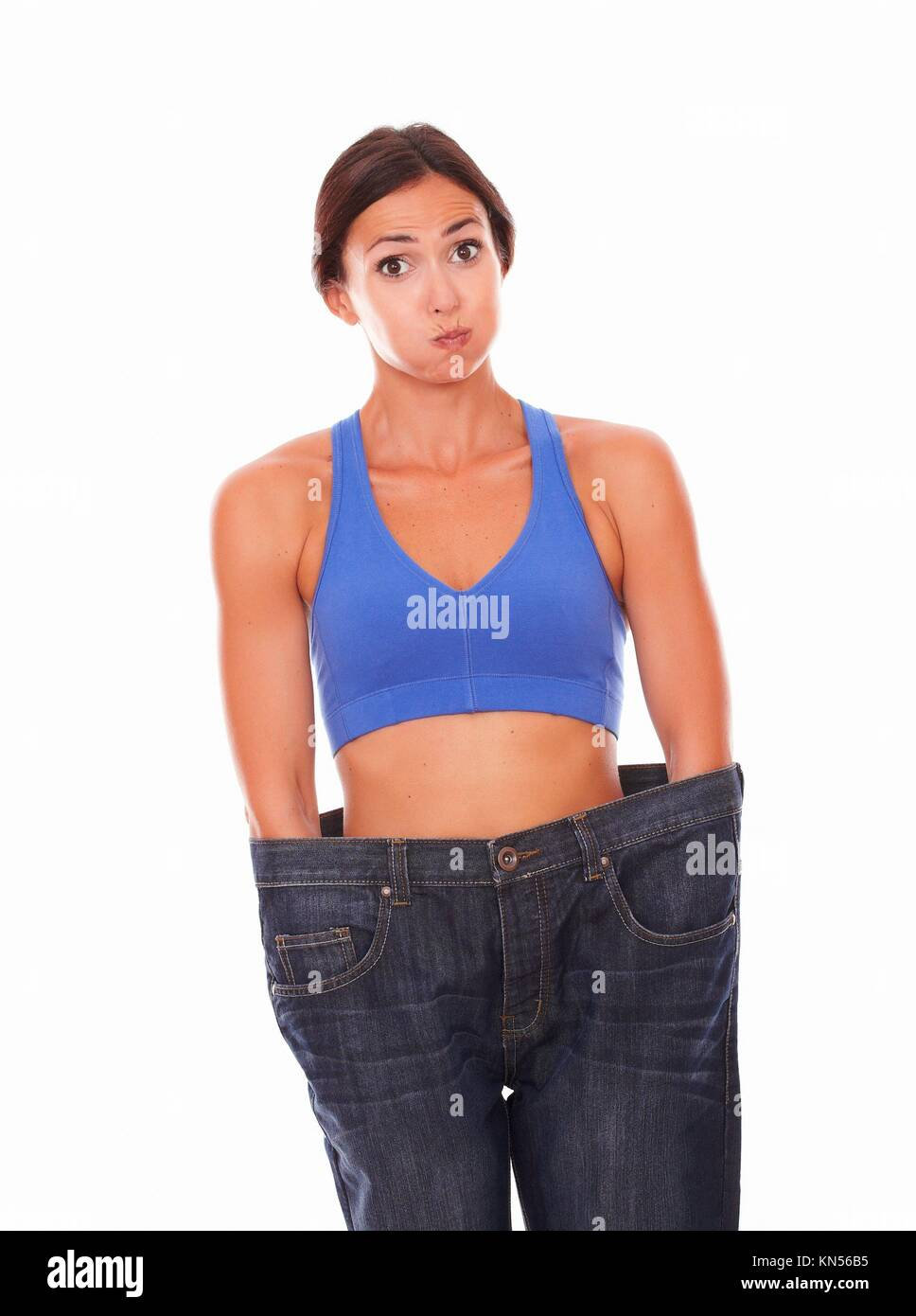 Brunette feeling satisfied with weight loss while is making a fanny face against white background. - Stock Image