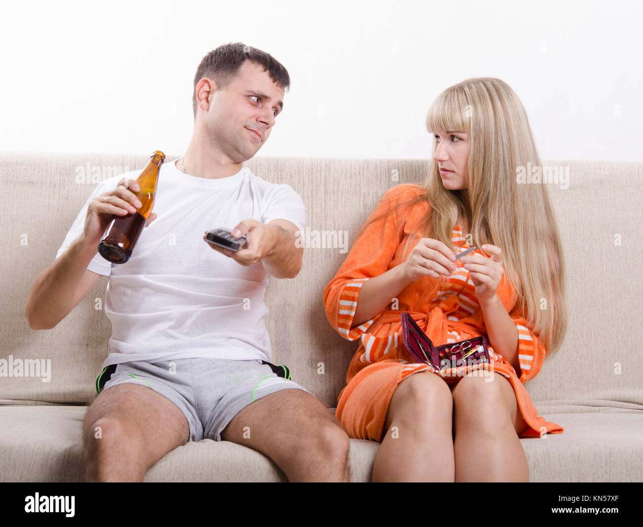 Couple sits on the couch. He is watching the TV, switch the channels with the remote, drinking beer, and grins, - Stock Image