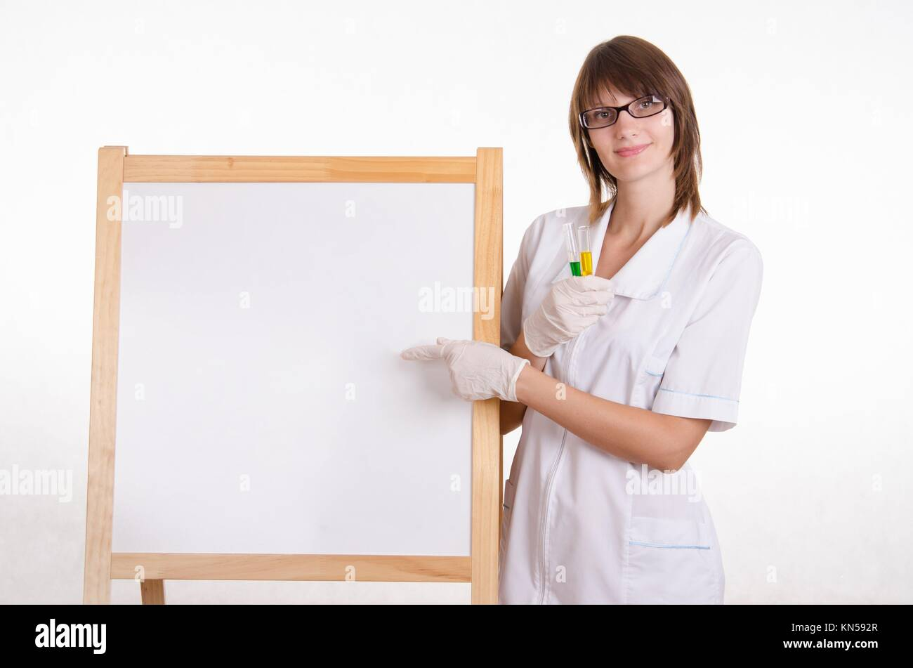 Chemist with test tubes stands at the blackboard with advertising. - Stock Image