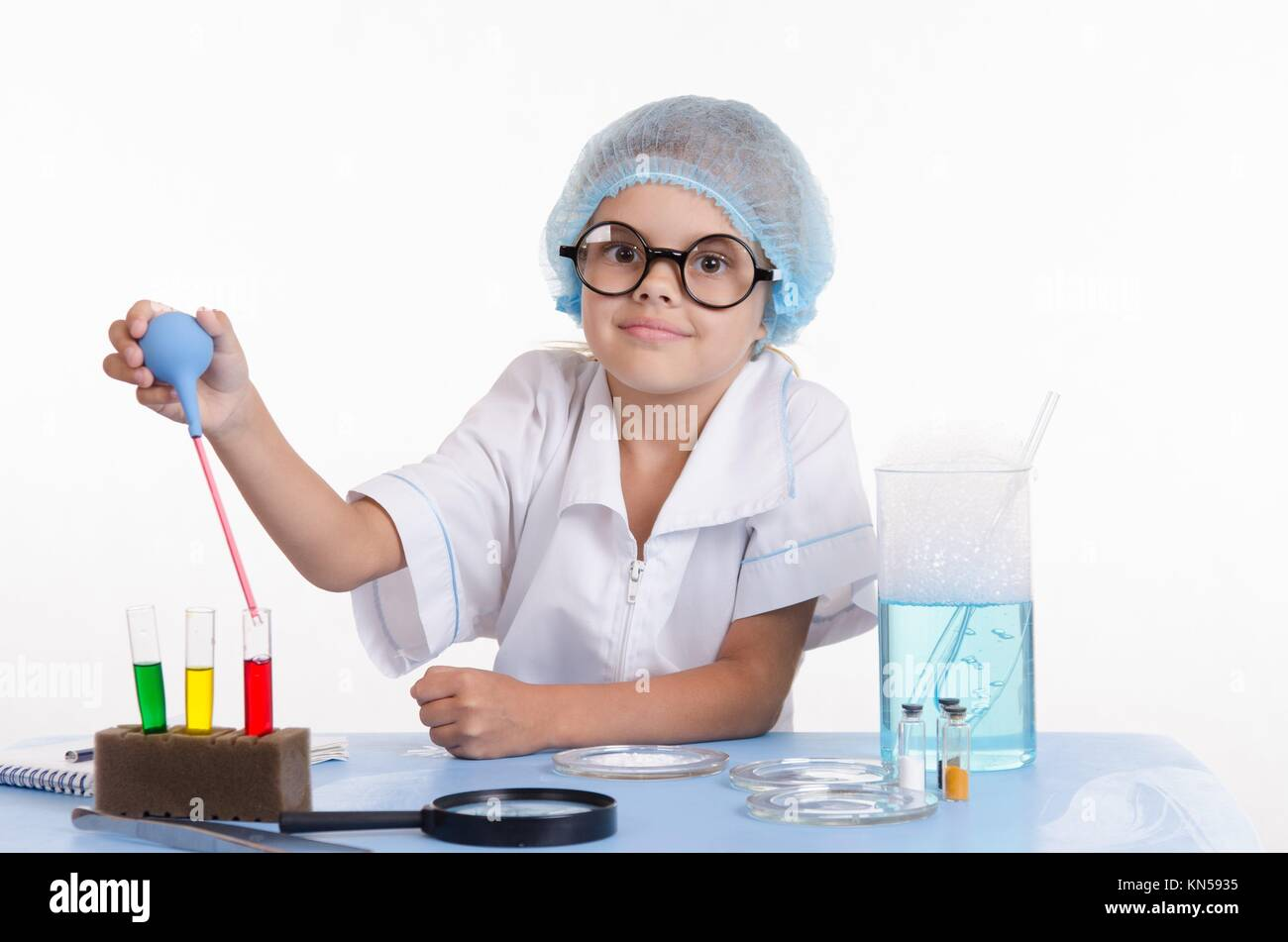 Chemist girl sitting at the table with the reagents in chemistry class and puts experiments. - Stock Image