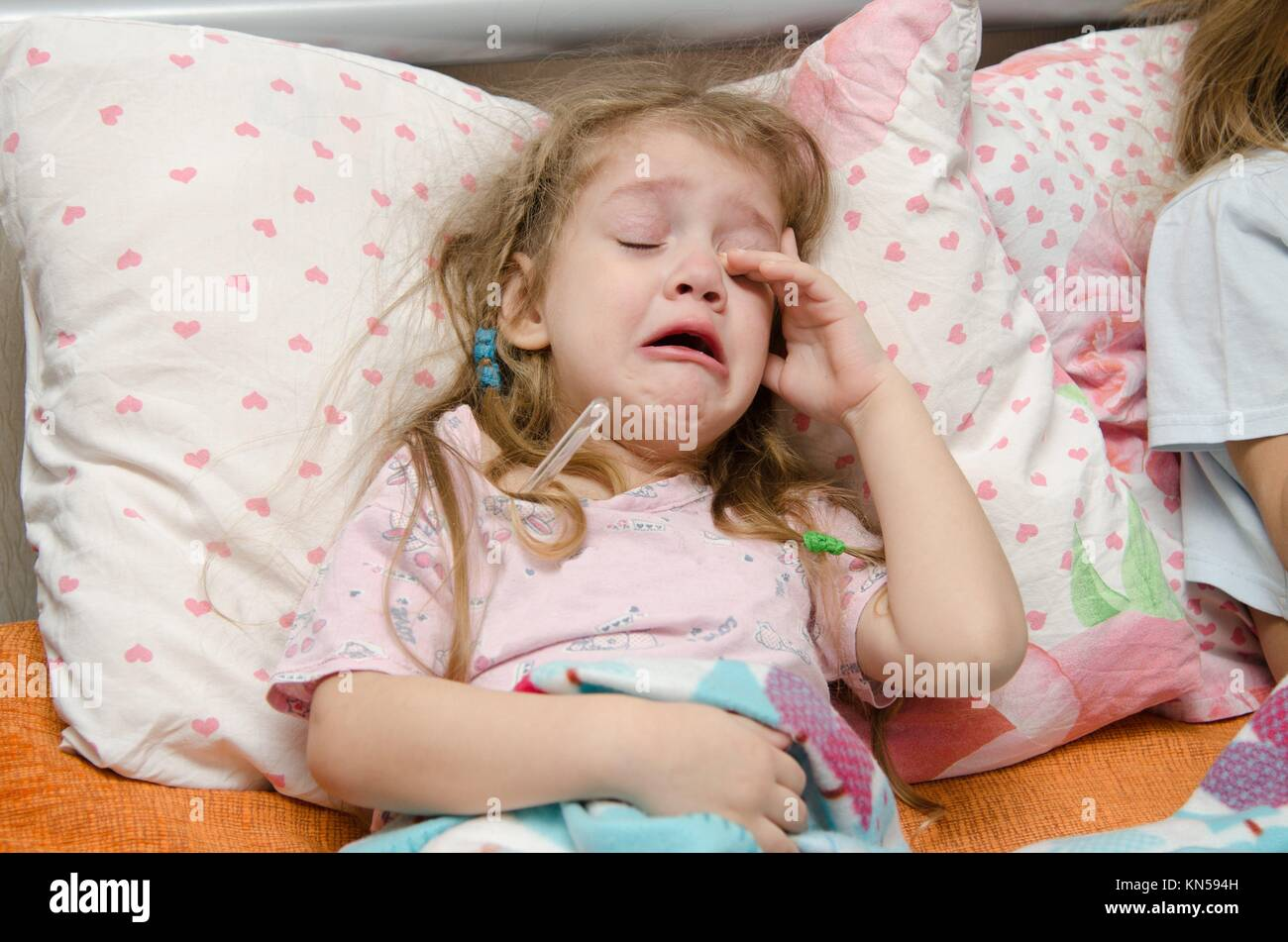 The three-year diseased girl lying in bed, Meria temperature thermometer, in a bad mood. - Stock Image