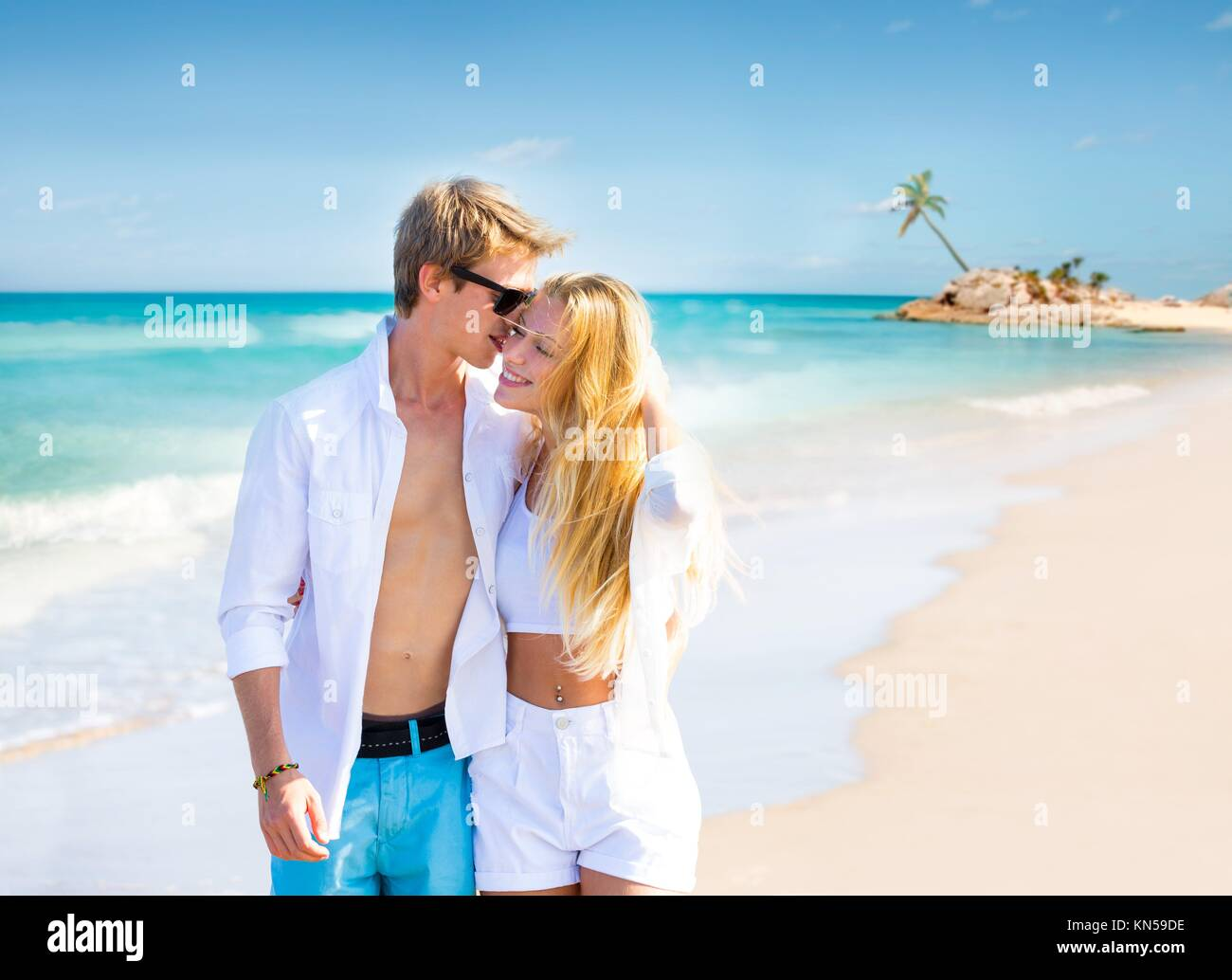 Blond teen couple walking together in the tropical beach at Caribbean sea in Mexico photo mount. - Stock Image