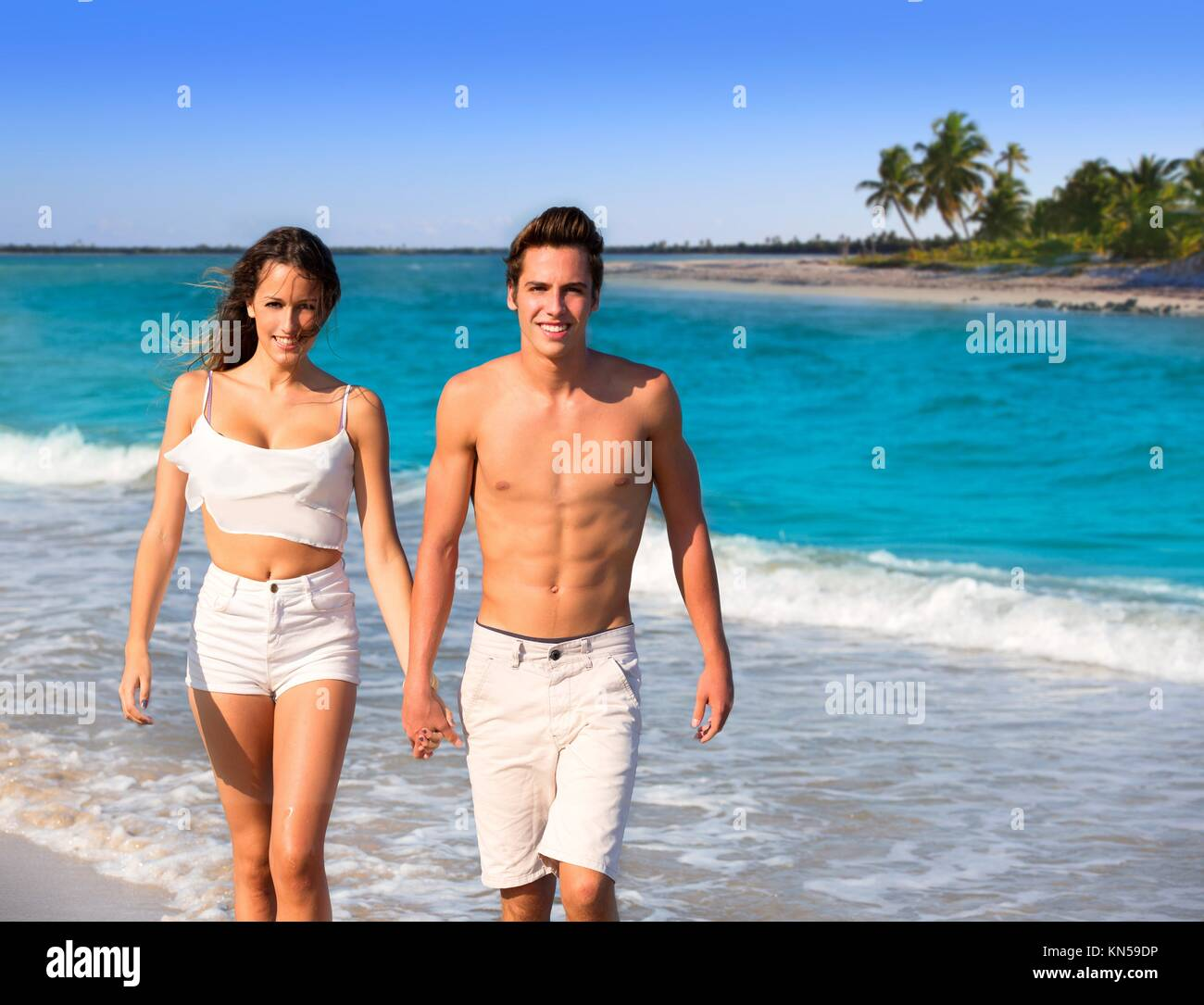 couple young tourists walking in a tropical Caribbean beach in Mexico photo mount. - Stock Image