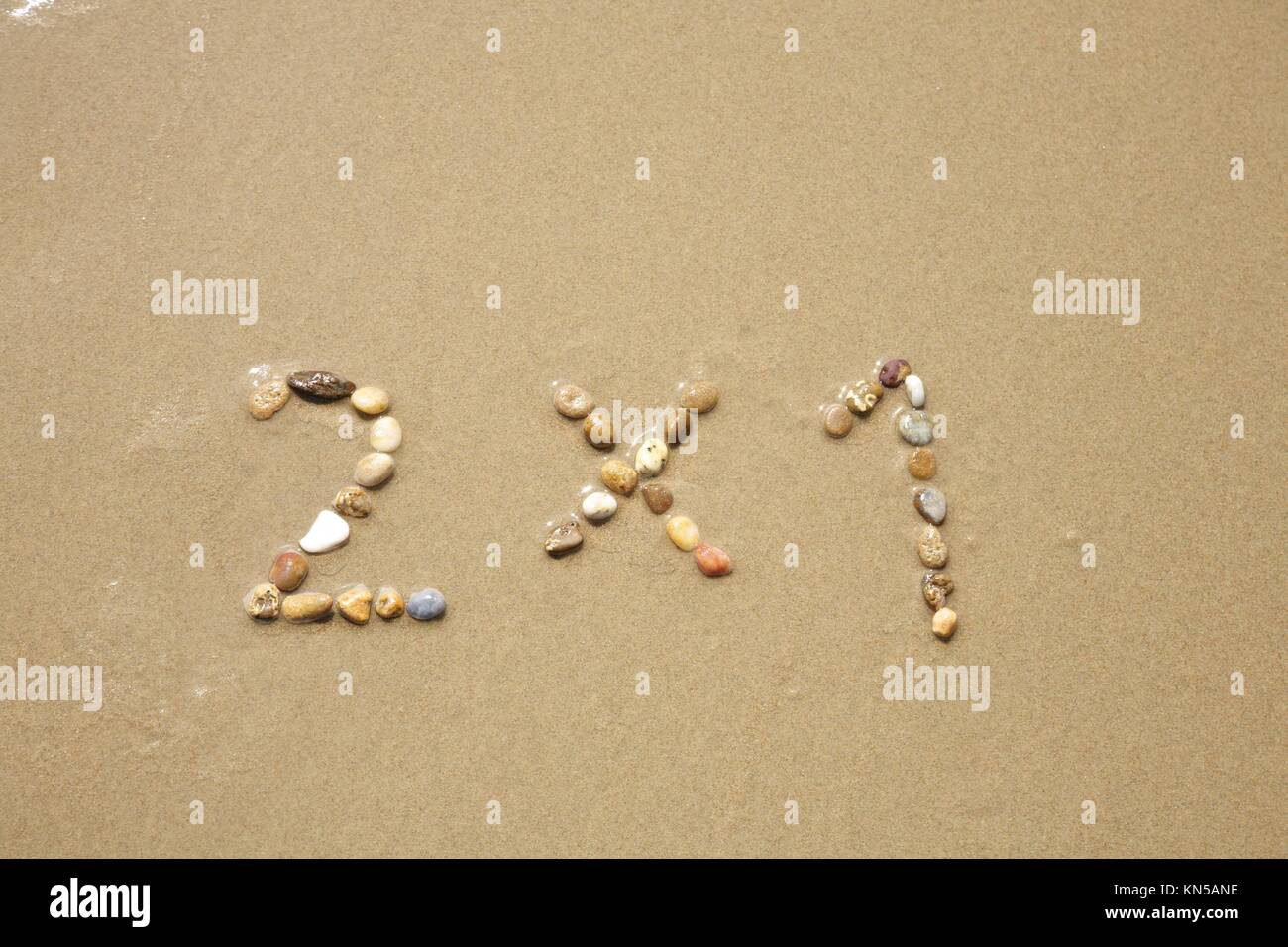 2x1 discount word writing with small stones on sand beach ground. - Stock Image